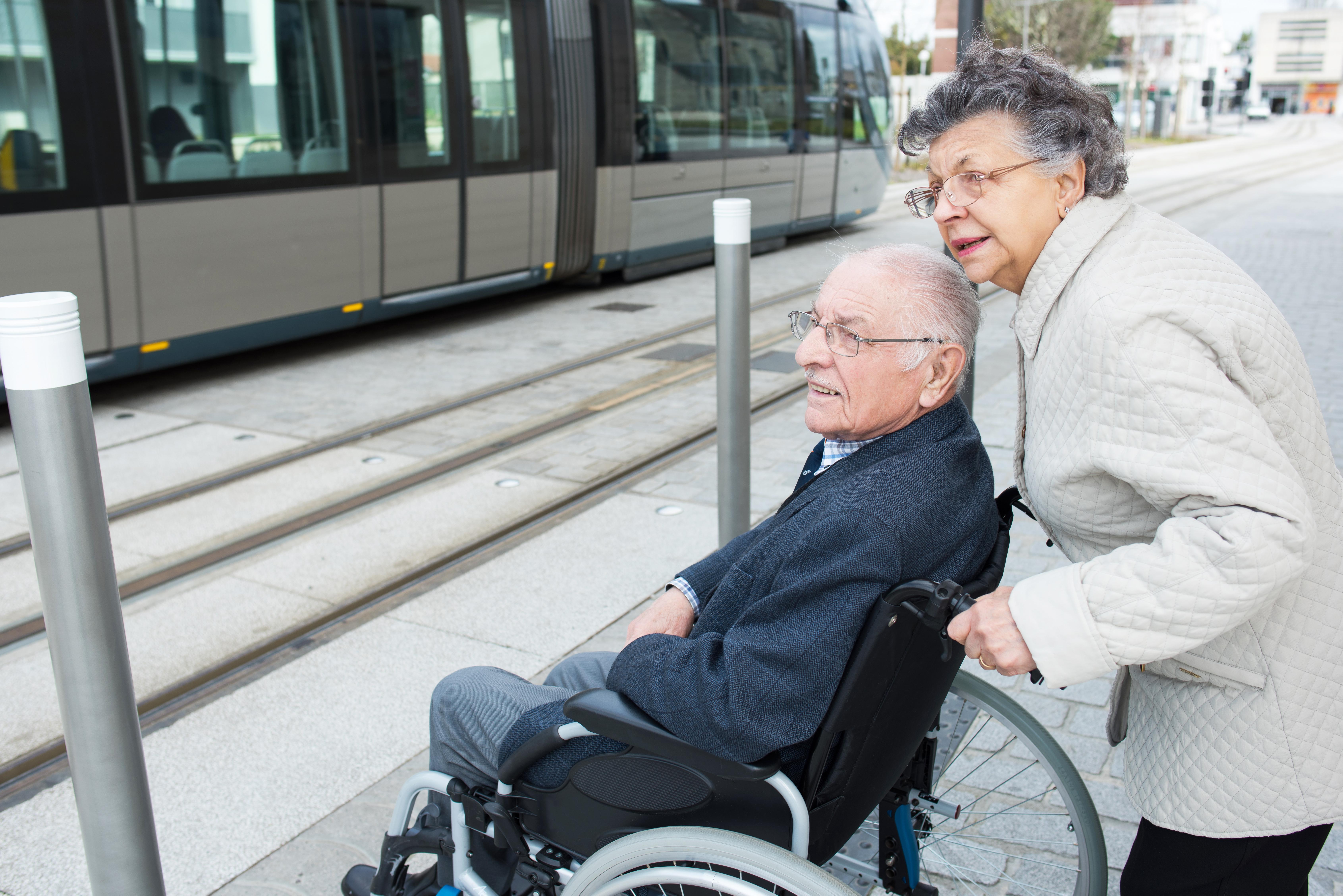 Woman pushung wheelchair AdobeStock 179199048